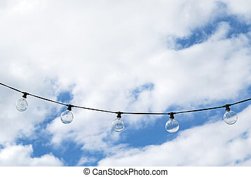 Big round Lightbulbs hanging in the air with blue cloudy sky...