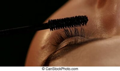 Makeup artist applying mascara. Black. Closeup - Makeup...