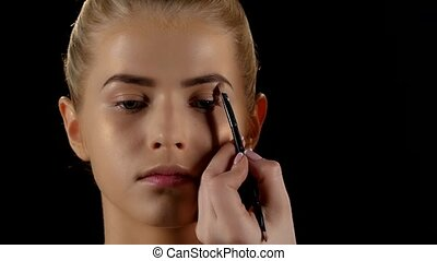 Doing make-up for a woman using eyebrows brush. Black. Closeup