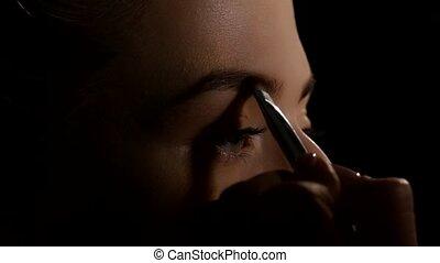 Coloring of shadows eyebrow. Black. Closeup - Coloring of...