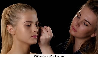 Makeup artist applying makeup to young blonde girl. Black....