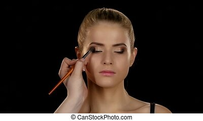 Makeup artist makes models eye makeup. Black. Closeup - Eye...