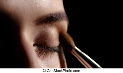 Artist applying eyeshadows. Black. Makeup. Closeup - Eye...
