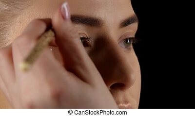 Making makeup Eyebrow Black Closeup - Beautiful girl getting...