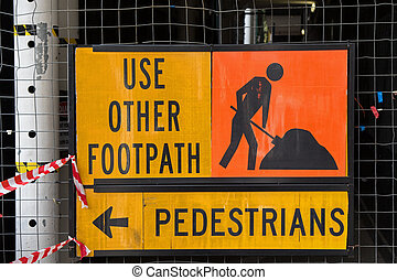 A sign for pedestrians to Use Other Footpath in yellow and...