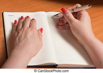 Female hands with manicure over pages of a notebook