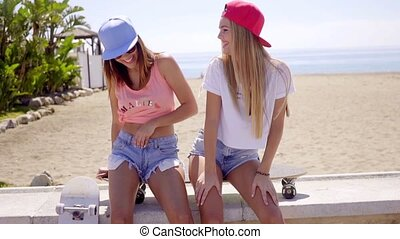 Two laughing friends in shorts sitting near beach - Two cute...