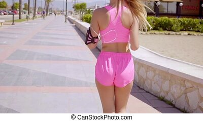 Back side of beautiful blond jogger by beach