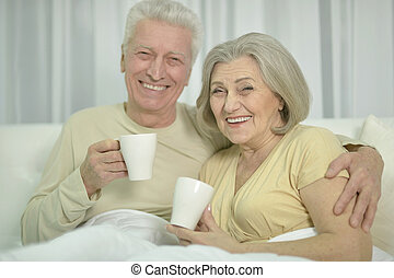 Senior couple in bed - Senior couple resting in bed with...