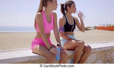 Two sporty young women pausing for a drink of bottled water...
