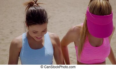 Two happy sporty young women relaxing in the sun in colorful...