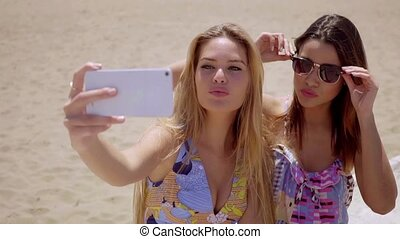 Playful young women posing for a selfie together on a mobile...