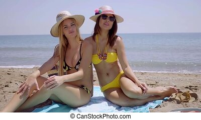 Two sexy young women sunbathing on a beach in their bikinis...