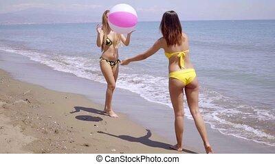 Two women in bikinis playing with a beach ball