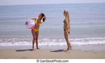 Two gorgeous young women posing with a beach ball on a...