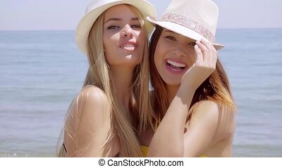 Two happy carefree young women on the beach