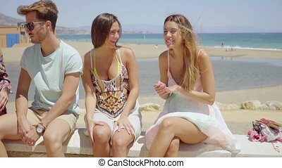 Young teenage friends in shorts talking near beach - Group...