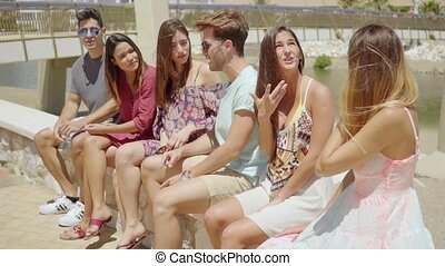 Group of male and female friends in shorts talking - Group...