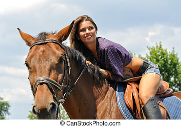 young attractive woman horseback riding in the summer sunny...