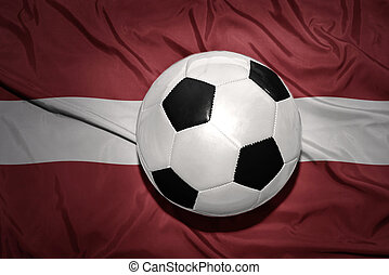 black and white football ball on the national flag of latvia...