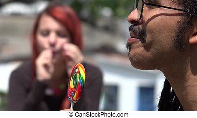 Man And Woman Eating Lollipops
