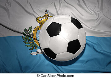 black and white football ball on the national flag of san...