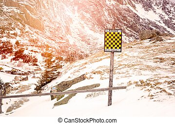 Avalanche sign in winter mountains with snow.