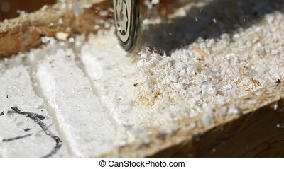 Sawdust fills the air as a carpenter uses a electric powered...