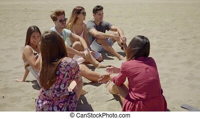 Group of diverse young people at the seaside sitting...