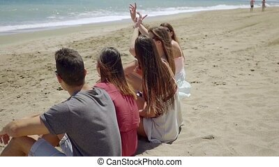 Backs of teens sitting on sandy beach outdoors - Backs of...