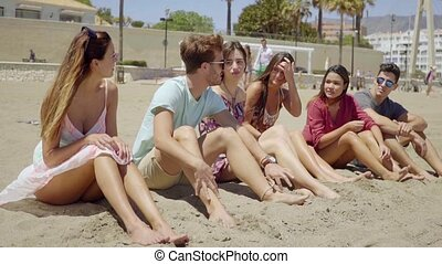 Teens talking and relaxing at sandy beach - Group of...