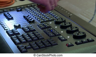 View of man's hand turns switches on control panel -...