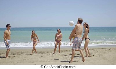 Group of young friends playing soccer on a beach - Group of...