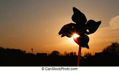 Pinwheel windmill against a sun. Windmill silhouette. Video...