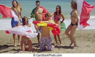 Group of Friends in Swim Suits with Flags at Beach - Group...