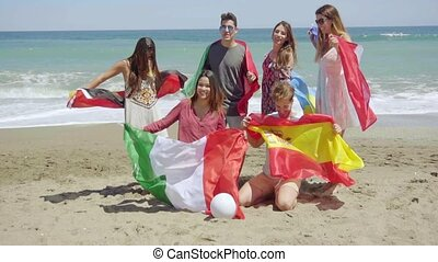 Group of Friends on Beach with Football and Flags - Full...