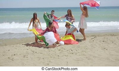 Group of Friends on Beach with Football and Flags