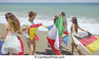 Group of Friends Carrying Flags on Sunny Beach - Group of...