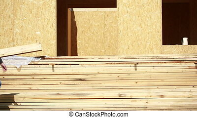 Young handsome builder with wood planks. building materials