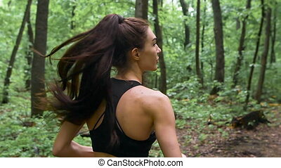 Young athletic sporty girl with long hair training in green...