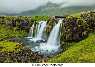 Threaded full-flowing waterfall on the mountains - Threaded...