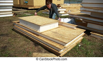 a man building a house. foam polystyrene. blocks made of plywood and insulation. housekeeping cottage. measurement tape