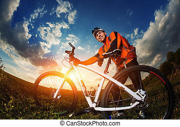 Man Cyclist with bike on sunset - Man Cyclist in Orange...