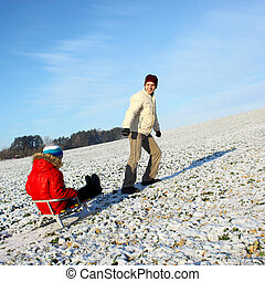 Dad pulls a child on a sled. Dad and son having fun in the...