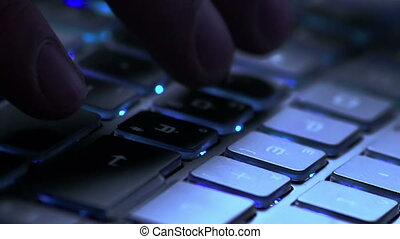 close-up of typing action on notebook keyboard with blue...