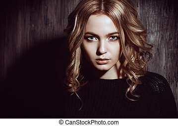 blonde curles - Casual teen girl standing by a grunge wall....