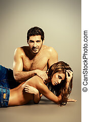 unisex jeans - Beautiful sexual couple topless playing in...