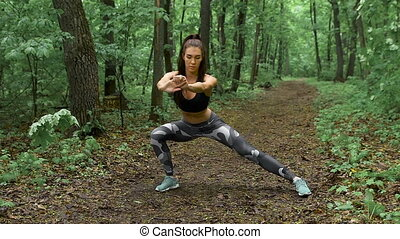 Slim fitness woman on a forest path The brunette with long...