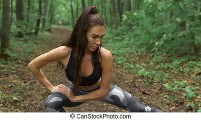 Slim fitness woman on a forest path. The brunette with long...