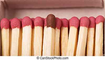 Single brown matchstick among red tones, out of the crowd...